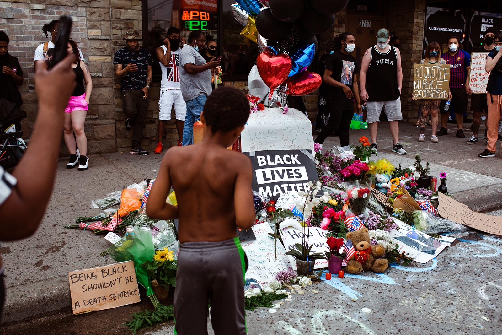Boy stands in front of memorial for George Floyd in Minneapolis