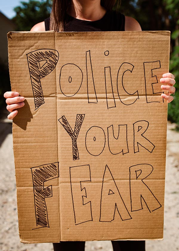 """Person holding """"police your fear"""" sign during George Floyd protests"""