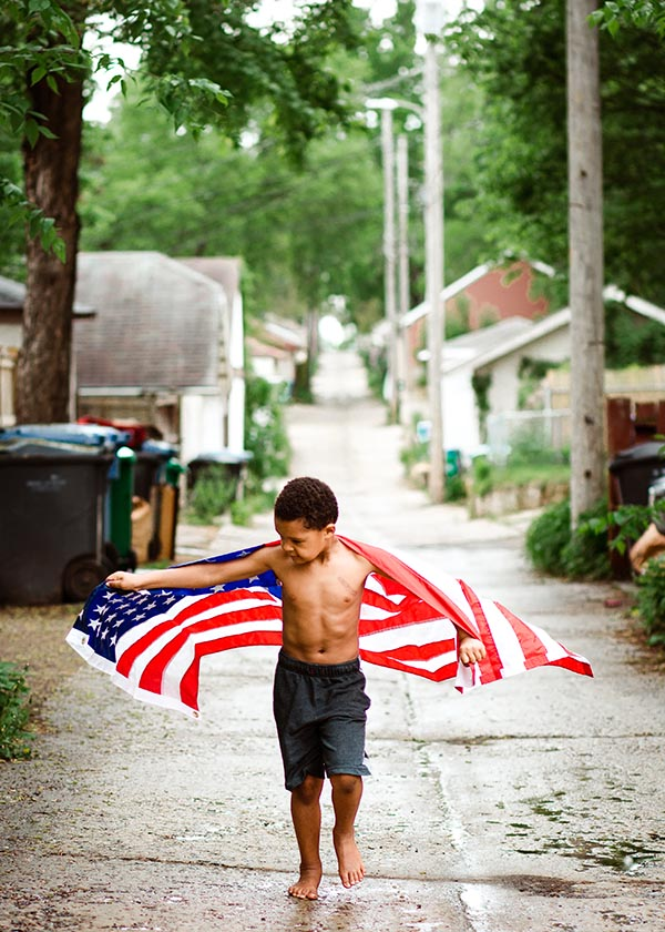 Child runs down street wrapped in American flag in Minneapolis