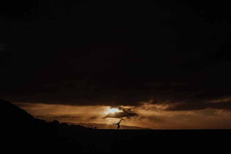 dark shadows photo contest winner, person doing cartwheel under dark sky