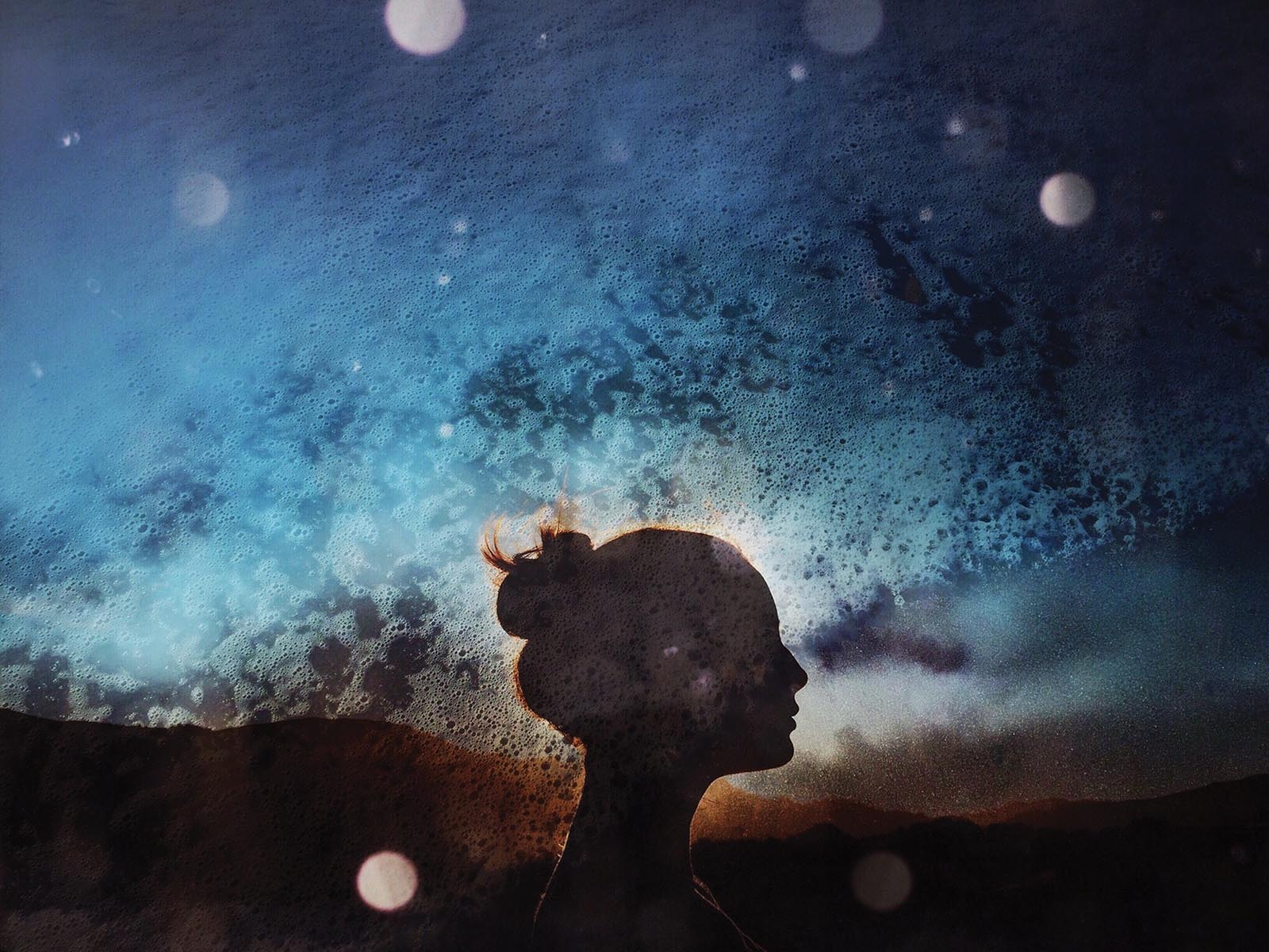 Creative photography of woman's head silhouette against sky