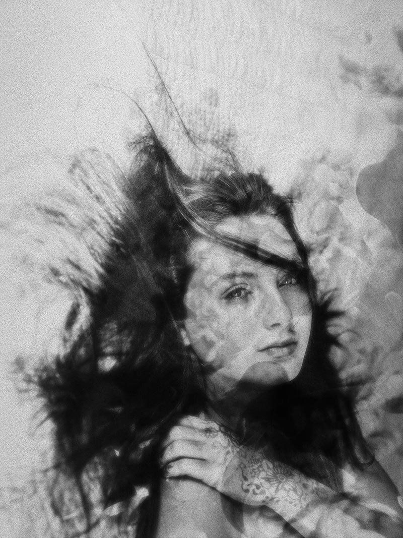 Black and white image of a girl's face with wild hair