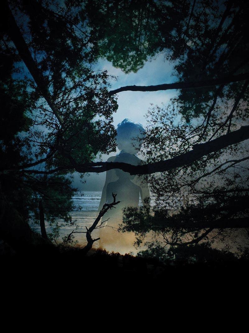 Creative double exposure of boy in woods