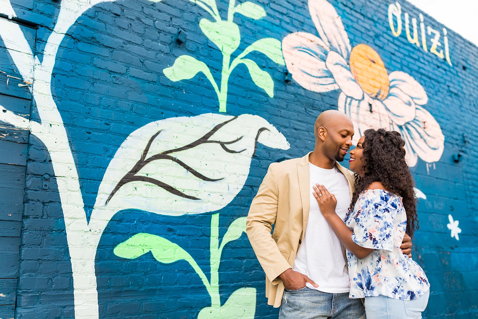 Couple photos in front of painted wall by Mecca Gamble