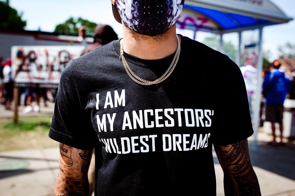 """Man wears black tshirt that says """"I am my ancestors' wildest dreams"""""""
