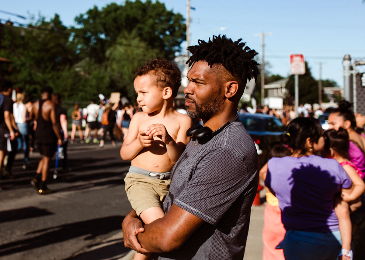 Black man holds his son during George Floyd protest in Minneapolis