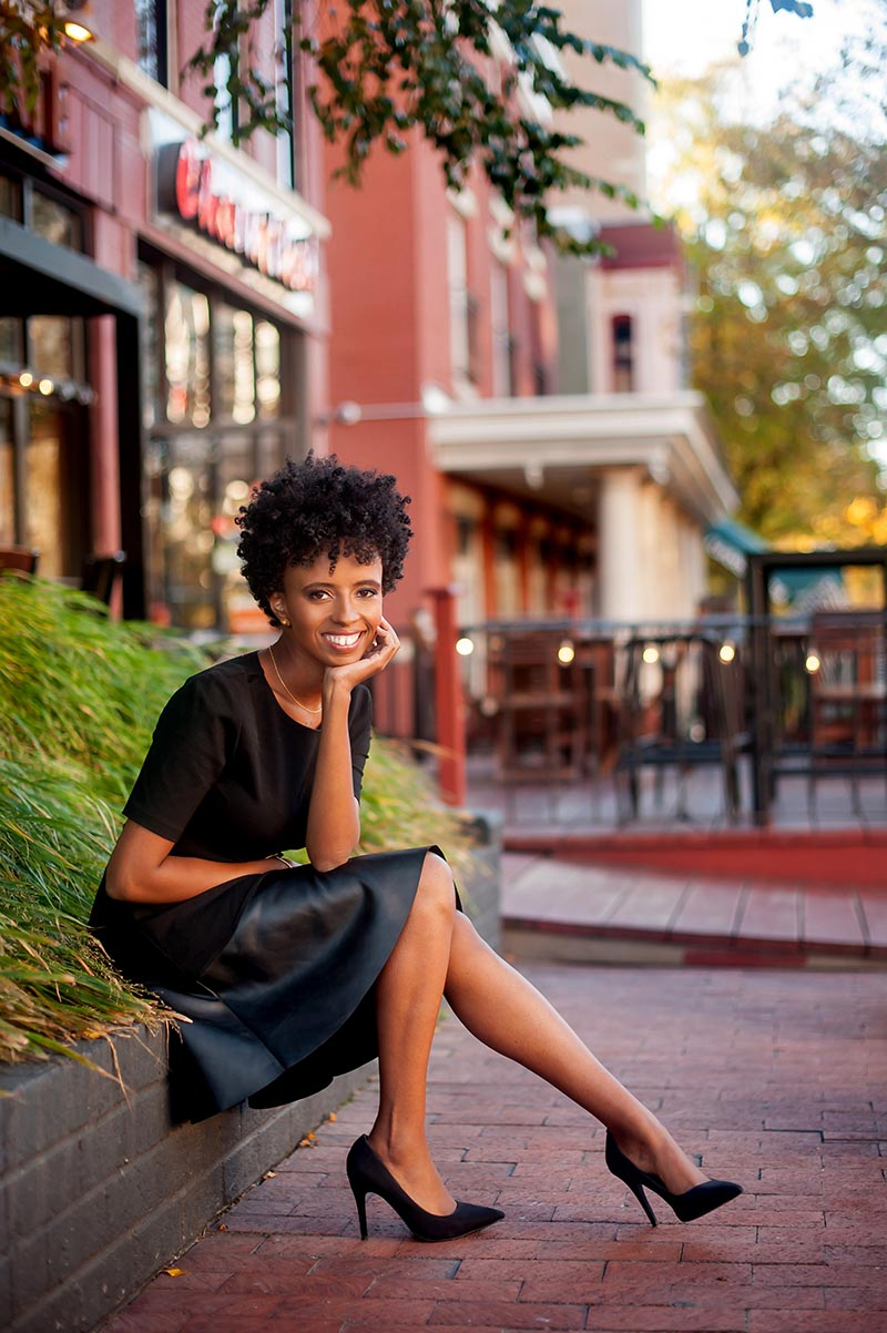 Lifestyle business portrait of a Black woman sitting on brick ledge in city