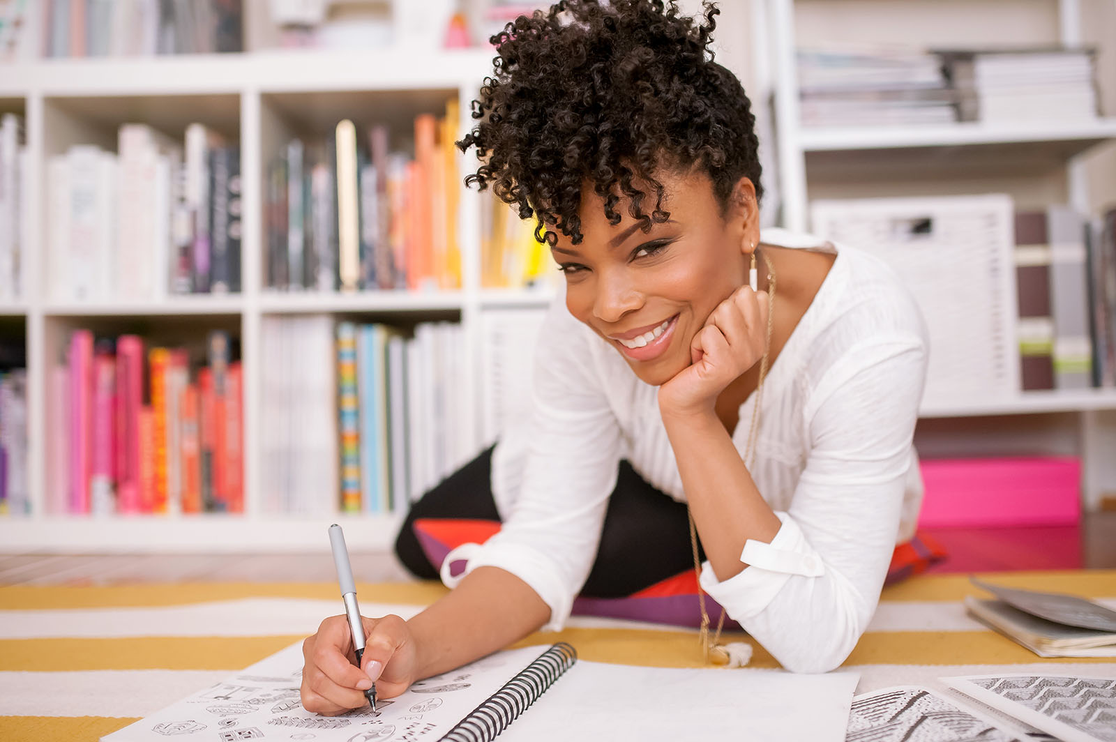 Lifestyle business portrait of a Black woman writing in notebook by Danielle Finney