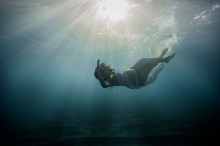 Pregnant woman in ocean during underwater maternity photo session
