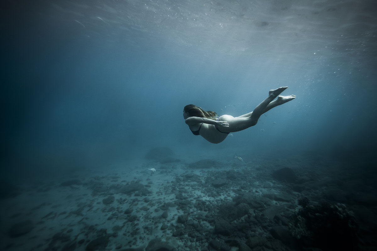 Pregnant woman underwater in ocean during underwater maternity photos