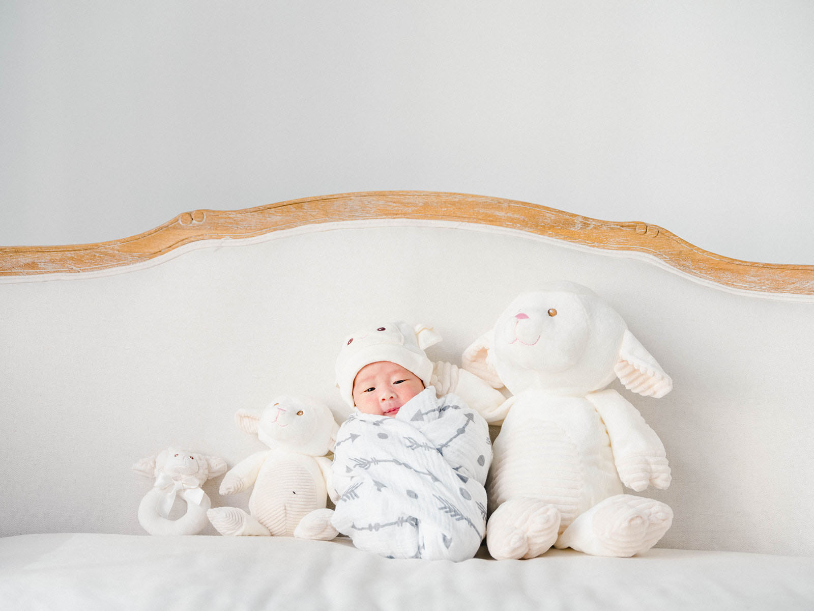 Baby on a bed with stuffies taken with Fujinon GF45-100mm f/4 R LM OIS WR lens