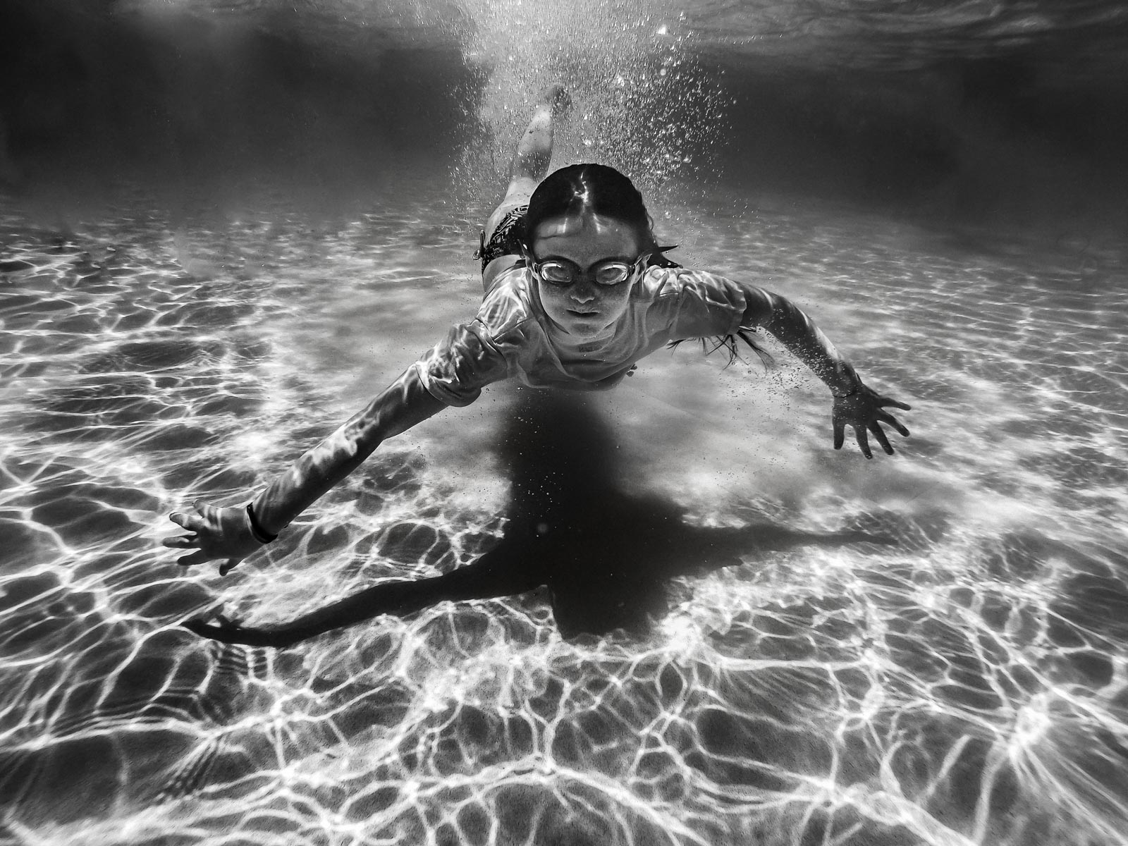 Summer black and white photo of a child swimming underwater