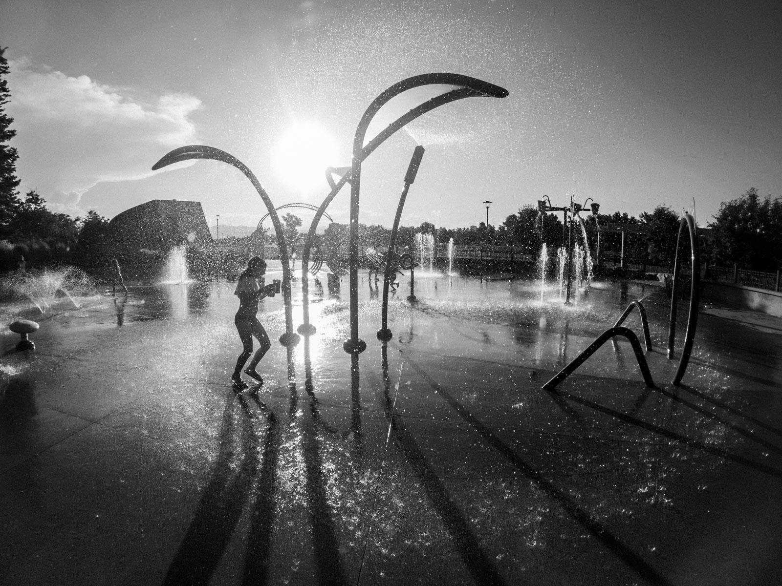 Summer black and white photo of child playing at splash pad