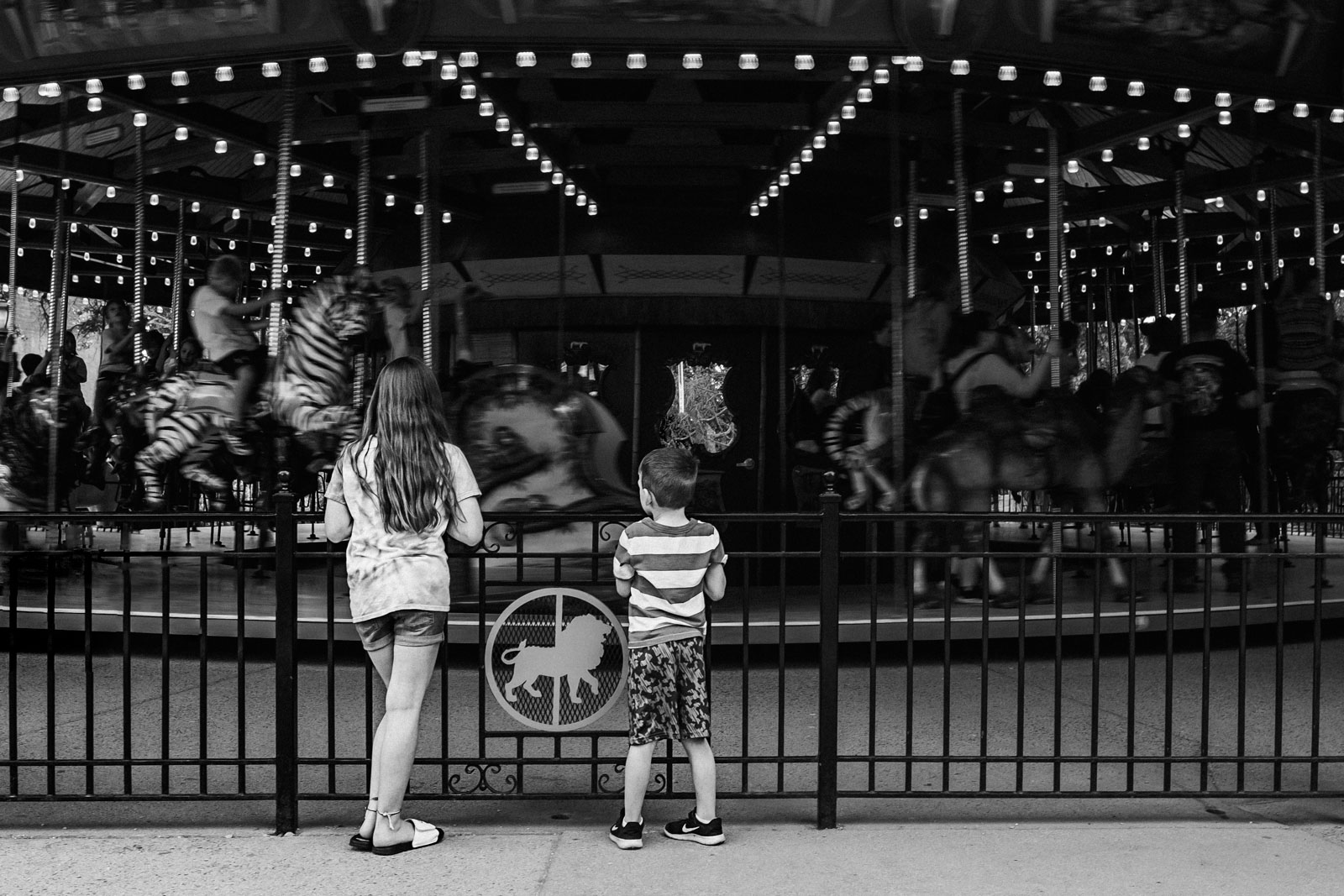 Black and white photo of kids watching carousel
