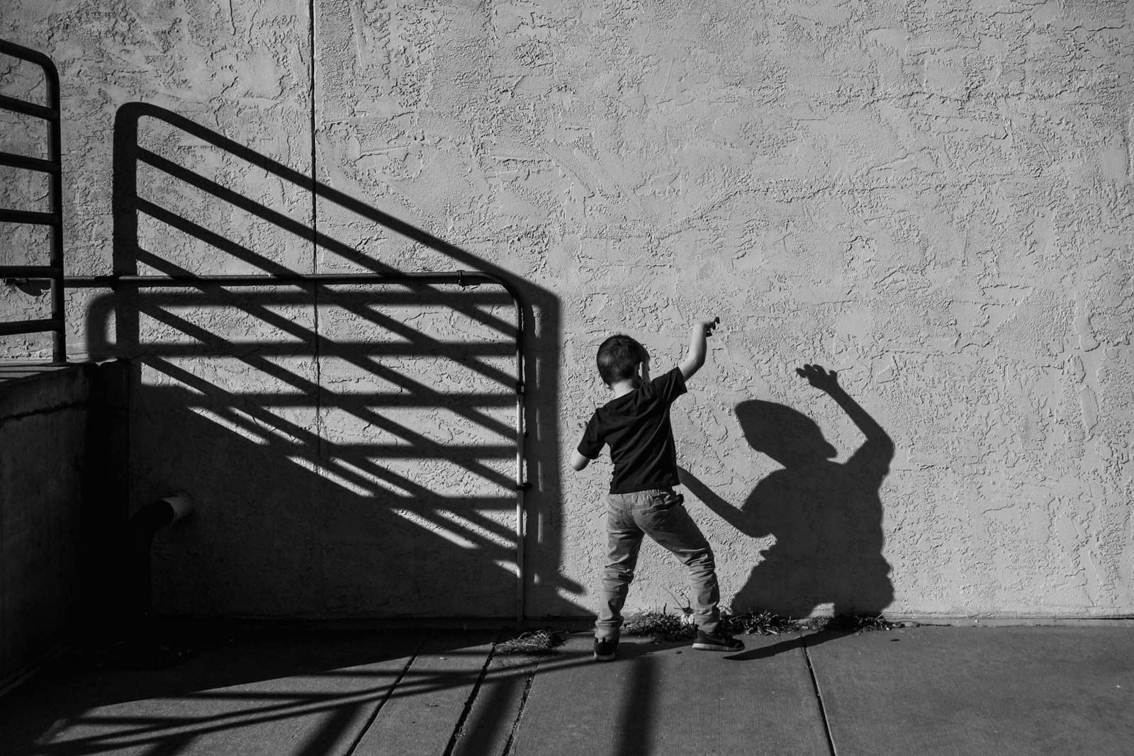 Boy plays with his shadow in black and white photo