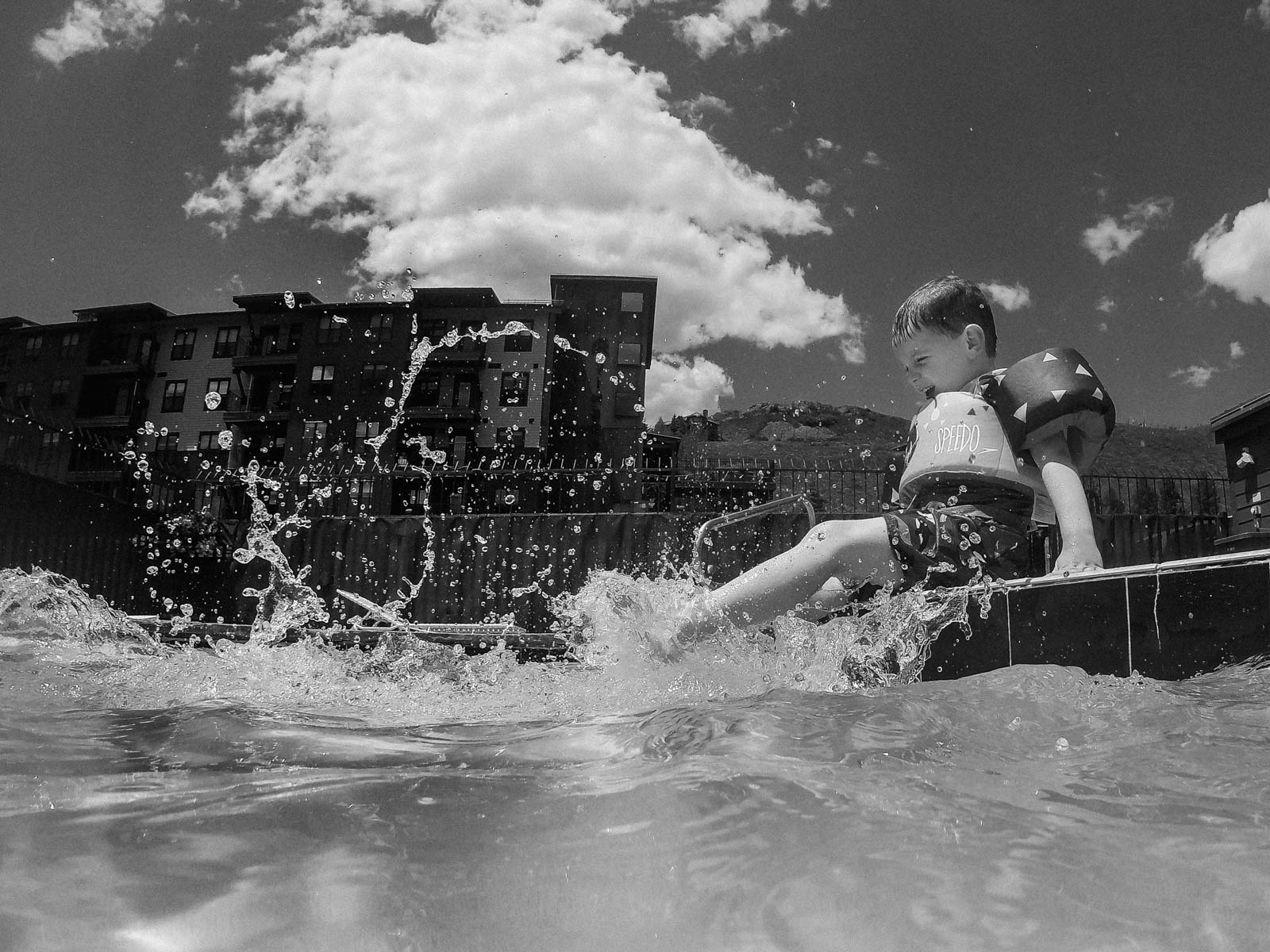 Black and white photo of child playing in water