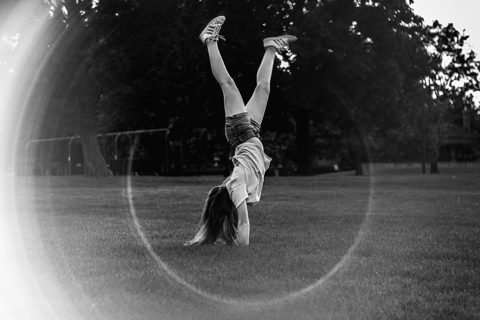 Summer black and white photo of girl doing cartwheel