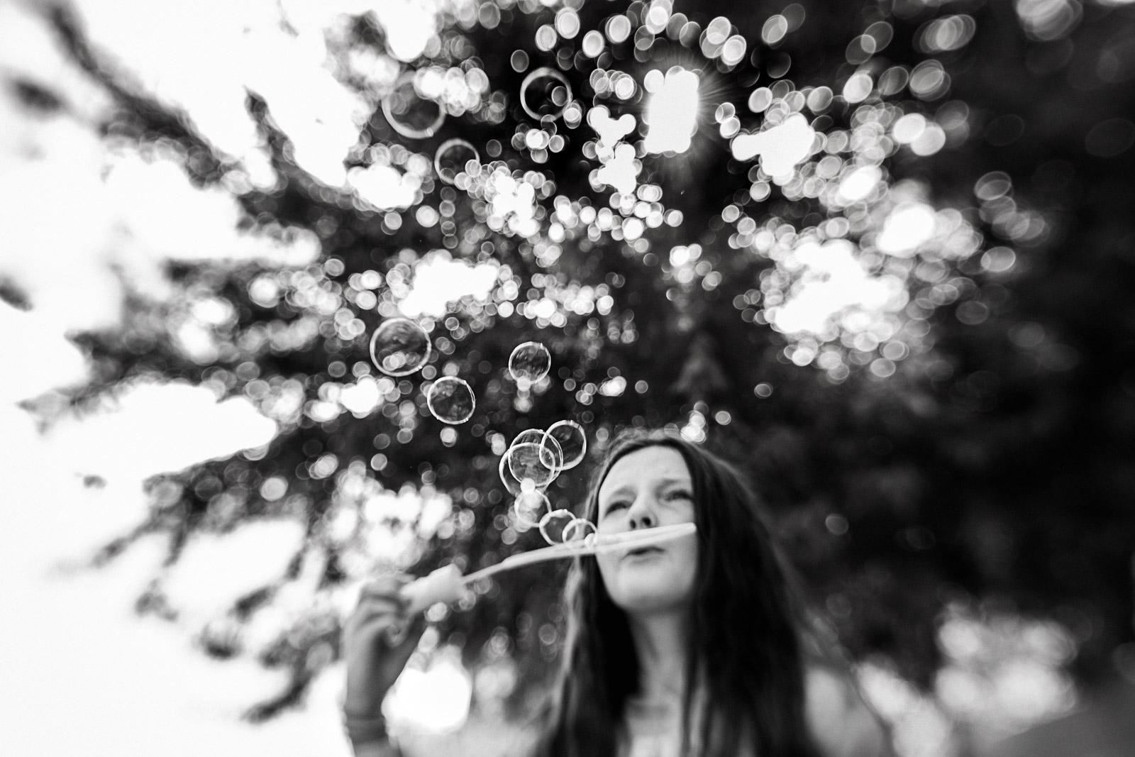 Summer black and white photo of girl blowing bubbles