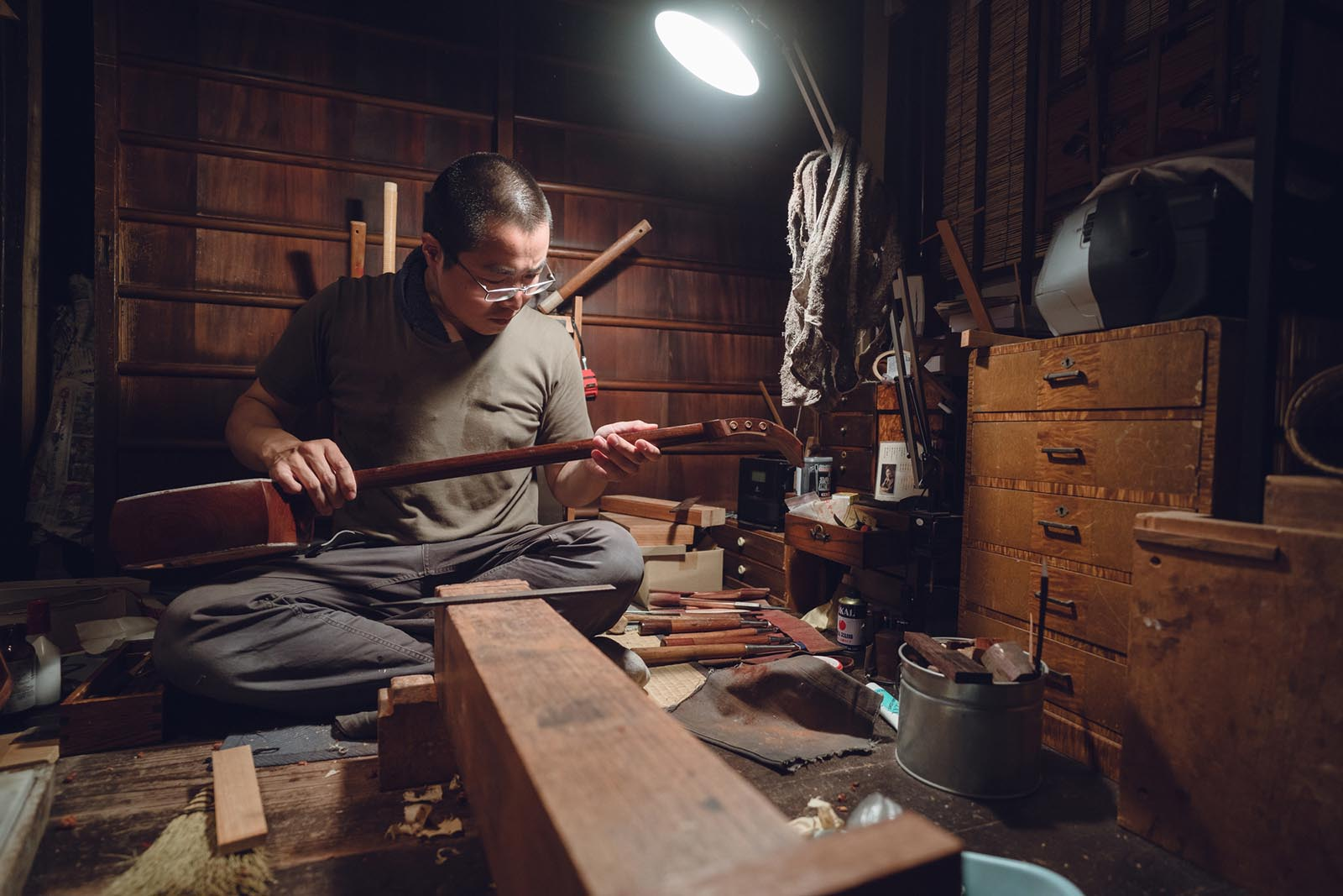 Photo of man in workshop under single light